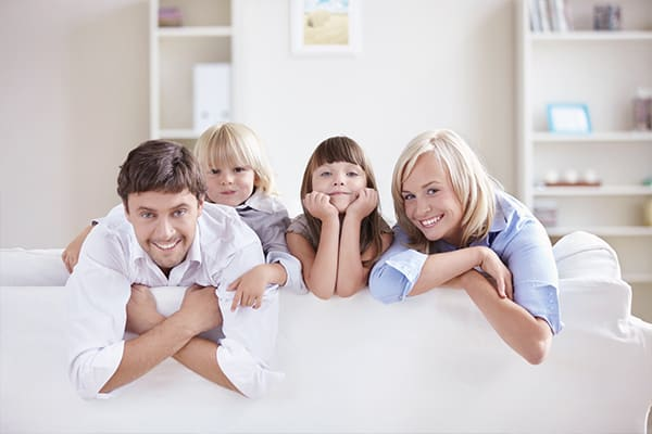smiling family on clean white sectional
